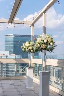 Вертикальный снимок двух ваз с красивыми цветами на белых колоннах на крыше здания