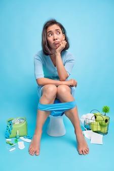 Вертикальный снимок несчастной задумчивой женщины, которая смотрит в сторону, сидит на унитазе, страдает от запора, много времени проводит в туалете, носит кружевные синие трусики, расстроенное выражение лица во время писания