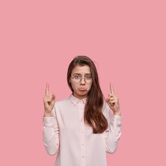 Вертикальный снимок несчастной молодой женщины, поджимающей нижнюю губу, показывает обоими указательными пальцами