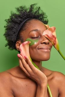 여성의 수직 사진은 눈을 감고 미소를 지으며 하이드로겔 패치를 부드럽게 적용하여 얼굴 스탠드 근처에 아름다운 꽃을 보유하고 있습니다