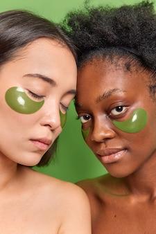 さまざまな肌の女性の垂直ショットは、鮮やかな緑の壁に裸の肩を立て、目の下にヒドロゲルパッチを適用し、美容トリートメントを受ける細い線を減らします。スキンケア