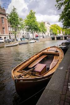 네덜란드 암스테르담에서 포착된 집들로 둘러싸인 운하 옆 목조 보트의 수직 샷