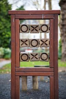 Вертикальный снимок деревянных крестиков-ноликов в парке