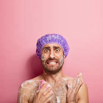 Вертикальный снимок встревоженного мужчины, который утром торопится, моет тело гелем и губкой, носит водонепроницаемый головной убор, стоит голым в ванной, принимает душ
