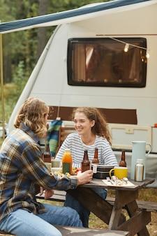 トレーラーバンのコピースペースでキャンプしながら屋外でピクニックを楽しんでいる若いカップルの垂直ショット