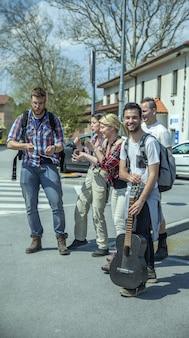 거리에서 노래하고 춤을 추는 젊은 행복 친구의 세로 샷