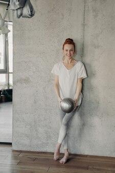 흰색 티셔츠와 레깅스를 입은 젊은 여성 발레 댄서가 벽에 기대어 작은 은색 핏볼을 들고 스튜디오나 교실에서 운동을 하는 모습을 세로로 촬영했습니다. 스포츠 컨셉