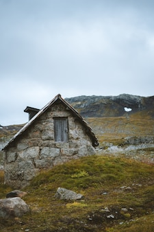 Vertical shot of an old abandoned cabin in a grassy field in finse, norway