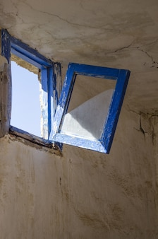 Vertical shot of an old rustic blue window about to break and fall in the dilapidated room