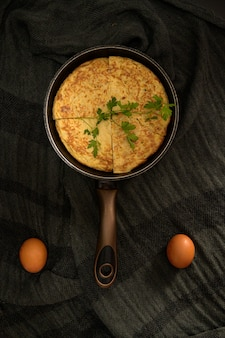 Vertical shot of an omelet divided into four pieces in a roaster and two eggs on the sides