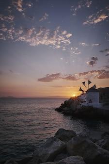 Colpo verticale del mulino a vento di ormos egialis nell'isola di amorgos, grecia al tramonto