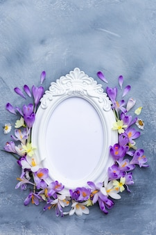 Vertical shot of an ornate white frame with purple and white spring flowers