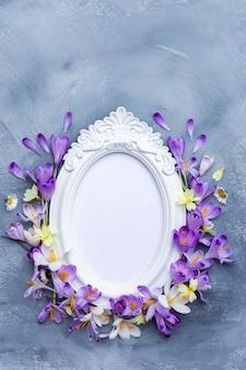 Colpo verticale di una cornice bianca decorata con fiori primaverili viola e bianchi