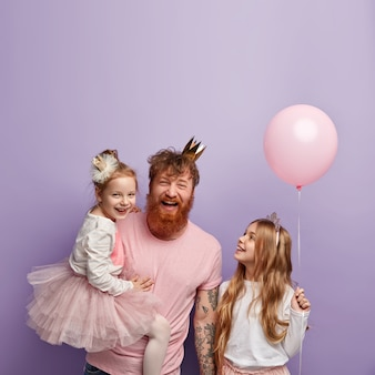 Vertical shot of overemotive joyful single dad and two daughters, celebrate fathers day, wear festive outfits