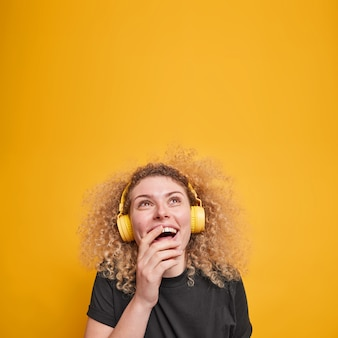 Il colpo verticale della donna dai capelli ricci felicissima guarda sopra con piacere tiene la mano sulla bocca indossa le cuffie stereo gode della playlist preferita vestita con una maglietta casual nera isolata sul muro giallo