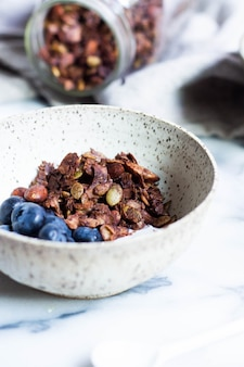 Vertical shot of paleo cocoa granola and blueberries in a white bowl with a blurred background
