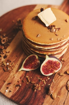 Vertical shot of pancakes with syrup, butter, figs and roasted nuts on a wooden plate
