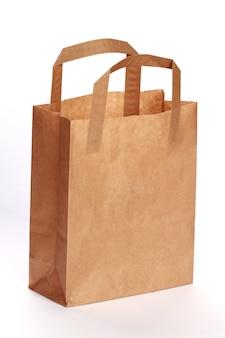 Ripresa verticale di un sacchetto di carta isolato su una stanza bianca