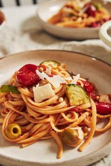 Colpo verticale di pasta con verdure e ingredienti sul tavolo bianco