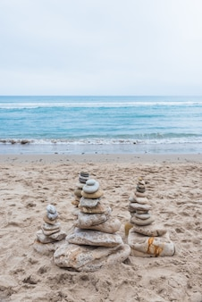 Colpo verticale di ciottoli impilati l'uno sull'altro in equilibrio sulla spiaggia