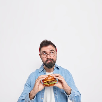 Il colpo verticale dell'uomo barbuto pensieroso tiene l'hamburger appetitoso messo a fuoco sopra pensa profondamente a qualcosa