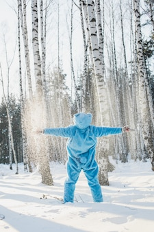 Vertical shot of a person in a fluffy blue costume enjoying the sunlight