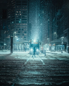 Vertical shot of a person in front of a train on a snowy road