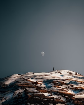 Vertical shot of a person hiking alone on scenic snowy hills