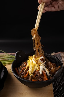 Vertical shot of a person holding cooked glass noodles with wooden chopsticks under the lights