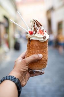 Colpo verticale di una persona che tiene un gelato di cronut a praga, repubblica ceca