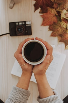 Vertical shot of a person holding a cup of coffee with a camera and leaves in the background