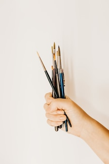 Vertical shot of a person holding a fistful of painting brushes