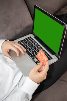 Vertical shot of a person inputting details of its credit card in the laptop
