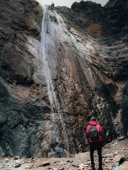 Vertical shot of a person in a red coat and a backpack looking at a high cliff with waterfall