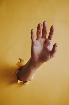 Vertical shot of a person's hand palm breaking through a yellow paper wall