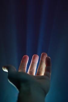 Colpo verticale della mano di una persona con una luce che brilla tra le dita