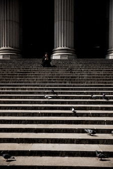 Vertical shot of a person sitting on stairs near columns
