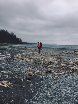 Vertical shot of a person standing on a rocky beach next to the ocean