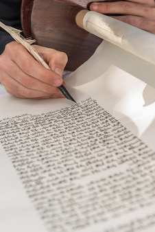 Vertical shot of a person writing with a feather on a scroll