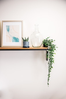 Vertical shot of a picture frame, house plants, and a transparent glass container on a white wall