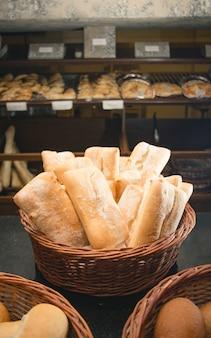 Colpo verticale di pezzi di pane in un cesto nel negozio