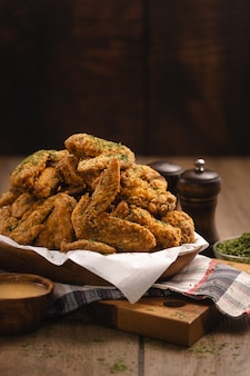 Vertical shot of a pile of fried chicken wings and some spices on a wooden table