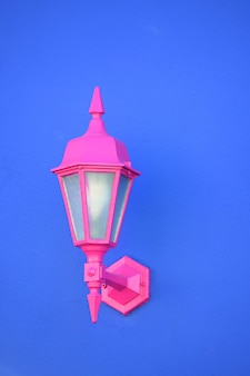 Colpo verticale di una lampada da applique rosa attaccata a una parete blu