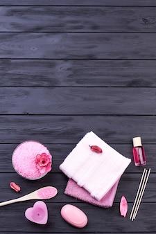 세로 샷 핑크 스파 트리트먼트 욕실 액세서리입니다. 나무와 복사 공간에 바디 케어 아이템.