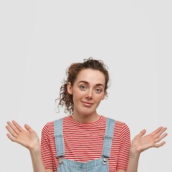 Colpo verticale di una donna dall'aspetto piacevole all'oscuro con i capelli ricci, ha un'espressione esitante, indossa una maglietta a righe con salopette, non sa rispondere alla domanda, isolato sopra il muro bianco