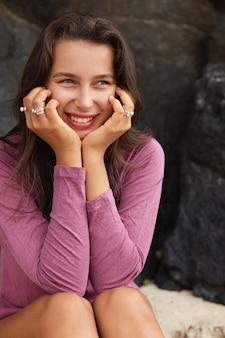 Colpo verticale di donna adorabile compiaciuta con un sorriso a trentadue denti, tiene entrambe le mani sotto il mento