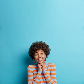Colpo verticale di felice giovane donna afroamericana tiene le mani sotto il mento focalizzate verso l'alto felicemente sogna qualcosa che indossa un maglione a righe casual isolato sopra la parete blu