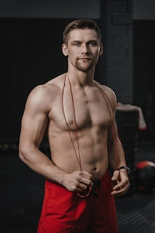 Vertical shot portrait of young handsome shirtless athlete at the crossfit gym wear red shorts with jumping rope on his neck looking at camera.