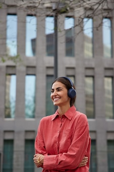 Vertical shot of positive dark haired millennial girl listens music in headphones while strolling in city wears red shirt keeps arms crossed looks happily away poses near modern building outdoors
