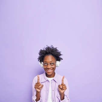 Vertical shot of positive dark skinned millennial girl with curly hair wears big transparent glasses listens music demonstrates blank copy space dressed in fashionable clothes isolated on purple wall